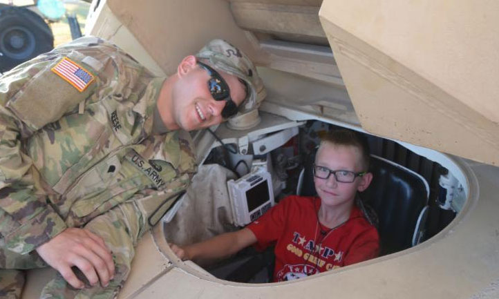 Army solider with Good Grief Camp kid