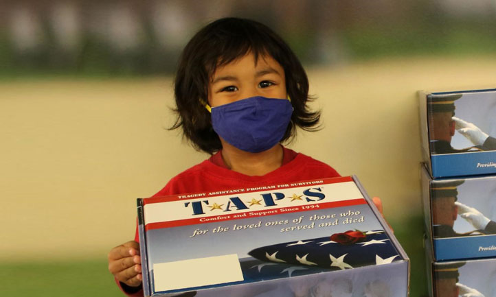 TAPS March Newsletter 2021 cover, Young child packing resourse kits