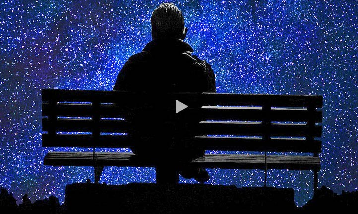 man at park bench at night